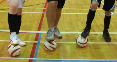 Photo des jambes de 3 joueurs avec 3 ballons de cécifoot dans un gymnase avec un plancher en bois.