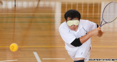 Un joueur de tennis adapté frappe la balle, un bandeau sur les yeux. Crédit pgoto Ayako Matsui.