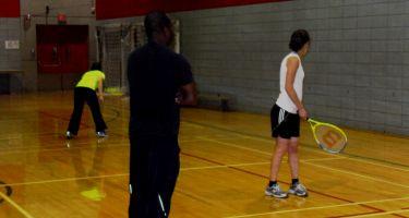 Julie et Jessica s'entraînent à lancer des balles contre le mur et à les rattraper, sous le regard attentif de Watson, leur entraîneur.