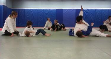 Les participants au cours de judo s'entraînent à faire des combats., en suivant les instructions de leur moniteur.