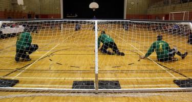 Trois athlètes en position défensive lors d'un match de goalball, photo prise derrière le filet.