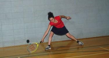 Jessica est en position pour frapper la balle dans un match de tennis sonore.