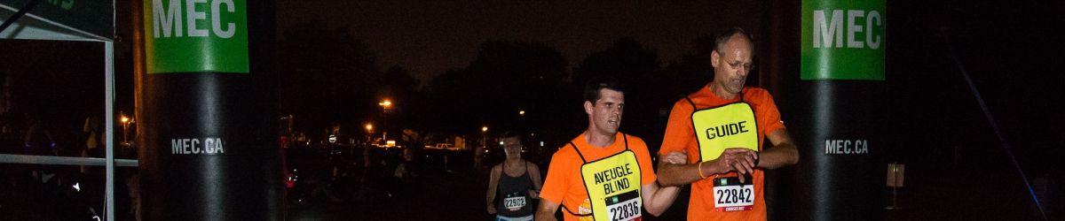 Josué Coudé et son guide en train de courir lors de la Course Lumière 2015.
