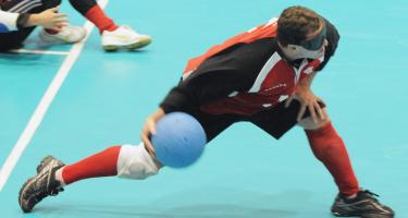 Bruno Haché capitaine de l'équipe canadienne masculine de goalball fait un lancer lors d'un match. Crédit-photo: Comité paralympique canadien.