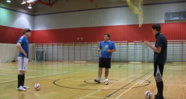 Un entraîneur explique les principes de base du cécifoot aux participants.