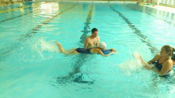 Photo d'un enfant pratiquant la natation avec son moniteur.