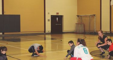 Photo d'enfants et moniteurs en train d'apprendre le goalball.