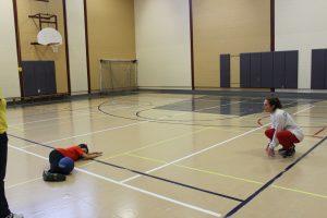 Photo d'un jeune faisant un arrêt de goalball devant la monitrice