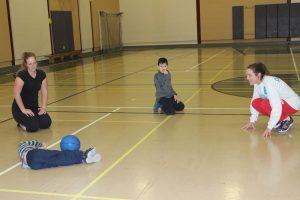 Photo d'un cercle d'enfants et de monitrices. Un enfant fait un arrêt de goalball.