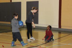 Photo d'un enfant par terre en train de regarder la monitrice, à côté d'un enfant tenant un ballon de goalball.