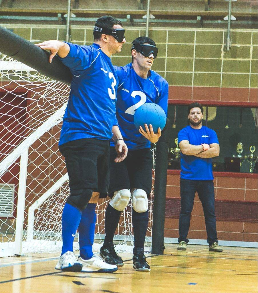 Joueurs de goalball en train de se passer le ballon devant leur filet.