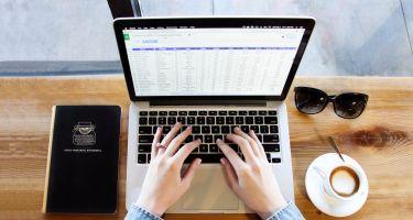 Photo de mains sur un ordinateur portable avec café, lunettes et carnet.
