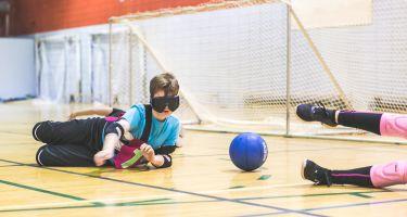 Un enfant couché au sol pour attraper le ballon avant qu'il arrive au but.