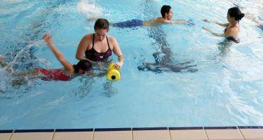 Deux jeunes dans la piscine accompagnés de deux entraîneurs.