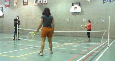 Deux personnes jouent au tennis à l'intérieur d'un gymnase.