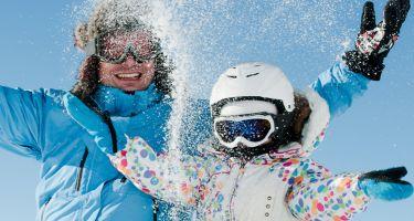 Un homme et une fille assis dans la neige en train de jouer, souriants.