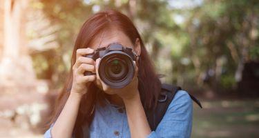Banner - Une femme photographe avec un appareil photo dans ses mains en regardant la camera.