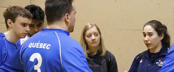 L'entraîneure en chef de l'équipe masculine de goalball du Québec, Nathalie Séguin, parle à Bruno Haché, Tristan Lépine-Lacroix, Raki Karim et Alexandra Piché lors d'un temps mort d'une partie de goalball.