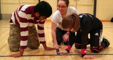 Les jeunes inscrits a l'activité de mini goalball, au Centre de réadaptation MAB-Mackay, en train de découvrir les lignes tactiles sur le terrain.