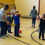 10. L'équipe camarades d'école fait à son tour le lancer de dos passant le ballon au-dessus de la tête.