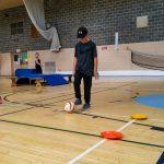 3. DSPM QC Habileté 29-09 - Liam en train de déplacer un ballon de cécifoot sur le terrain.
