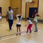 9. L'équipe « la Fratrie » apprend à lancer de dos en passant le ballon au-dessus de la tête.