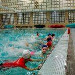 DSPM-Qc Petit échauffement de groupe avec des kicks de crawl sur le bord de la piscine.
