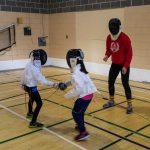 14. Lou-Félix et Amélie en train de combattre sous la supervision de Gabrielle, intervenante sportive.