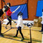 15. L'activité est presque terminée. Pour terminer, les enfants font de petits combats avec des épées mousses. En avant, Loup-Yann, instructeur, et Lou-Félix jouent ensemble.