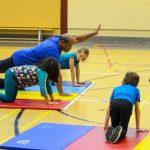 23. Pour travailler les abdos et l'équilibre, Thiar explique un nouveau mouvement. Les enfants sont à quatre pattes et devront lever la main gauche et la jambe droite.
