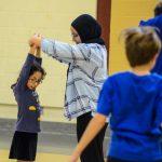 29. Asma, intervenante sportive, aide Sarah à correctement étirer ses bras vers le ciel.