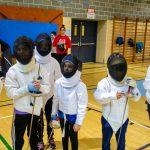 6. Une photo de tous les participants dans leur tenue d'escrime. De gauche vers la droite Elyana, Kelly-Anne, Madeleine, Lou-Félix, Amélie et Liam.