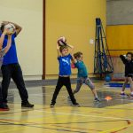 7. Thiar, l'instructeur, explique aux enfants comment lancer à deux mains au-dessus de la tête.