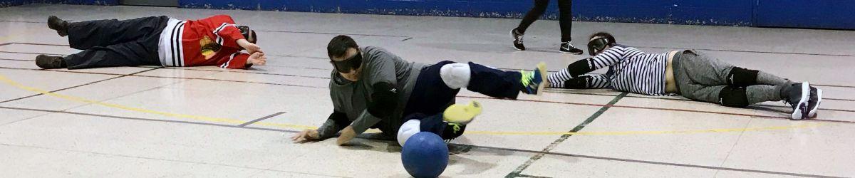 Trois joueurs de goalball au sol en position défensive. Le joueur du centre arrête le ballon avec ses jambes.
