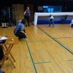 19. Des bénévoles de la compétition (un marqueur, un juge de but et l'arbitre) en dehors du terrain avec les trois membres de l'équipe de Phurax sur le terrain.