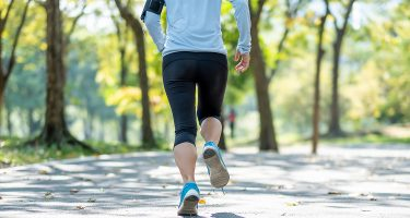 Femme en train de courir dans un parc.