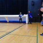 11. Oyana avec le ballon dans la main droite et sa main gauche sur le but pour se repérer dans l'espace.