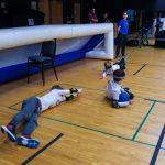 14. Les trois membres de l'équipe des Phurax couchés au sol. Le joueur du centre protège le ballon avec son corps suite à un arrêt.