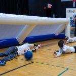 13. Les trois membres de l'équipe des Phurax couchés au sol en position défensive, en train de bloquer le ballon.