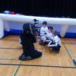 17. L'équipe des Phurax, à genoux devant leur but, en train de faire une entrevue avec un caméraman.