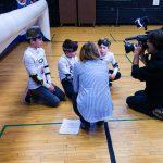 18. L'équipe des Phurax, à genoux devant leur but, en train de faire une entrevue avec une journaliste et un caméraman.