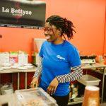 TIGM2019-Naomie est dans la cuisine et sourit en regardant vers sa droite.