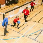 TIGM2019-Une joueuse de l'Alberta s'apprête à lancer le ballon. On voit les 3 athlètes de l'Alberta et un juge de but.