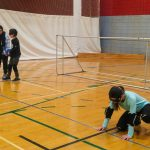 11. Mini-goalball Hiver 2019 - Mathys se prépare à lancer le ballon sous la supervision d'Asma, intervenante sportive.