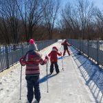 4. Alba, Rym et Edgar, dos à la photographe, traversent le pont qui relie l'Île-de-la-Visitation et Montréal.