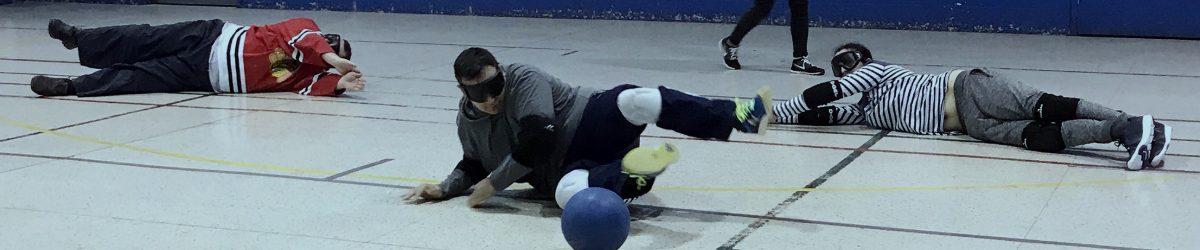 Image : Des joueurs de goalball sur un terrain en position défensive en train de faire un arrêt. On lit le texte suivant : Changements au goalball récréatif hiver 2019, tous les détails au www.sportsaveugles.qc.ca