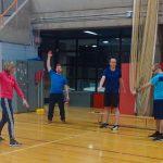 Les trois participants et l'instructrice s'échauffent en faisant des rotations des bras.