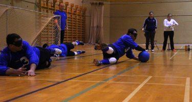 Les trois athlètes de l'équipe québécoise de goalball au sol en position défensive. Simon Tremblay bloque le ballon avec son corps, il prend le ballon avec ses mains. Nathalie Séguin (entraîneure-chef) et Mario Caron (juge de but) regardent attentifs.