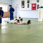 Du sport pour moi! Montréal - Judo. Sarah, Rym, Sofia et Edgar rampent en avançant seulement avec les bras, sous le regard des entraineurs Vincent et Stéphane.