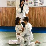 Du sport pour moi! Montréal - Judo. Sofia et Edgar qui se préparent à combattre et Louiza qui les observe.